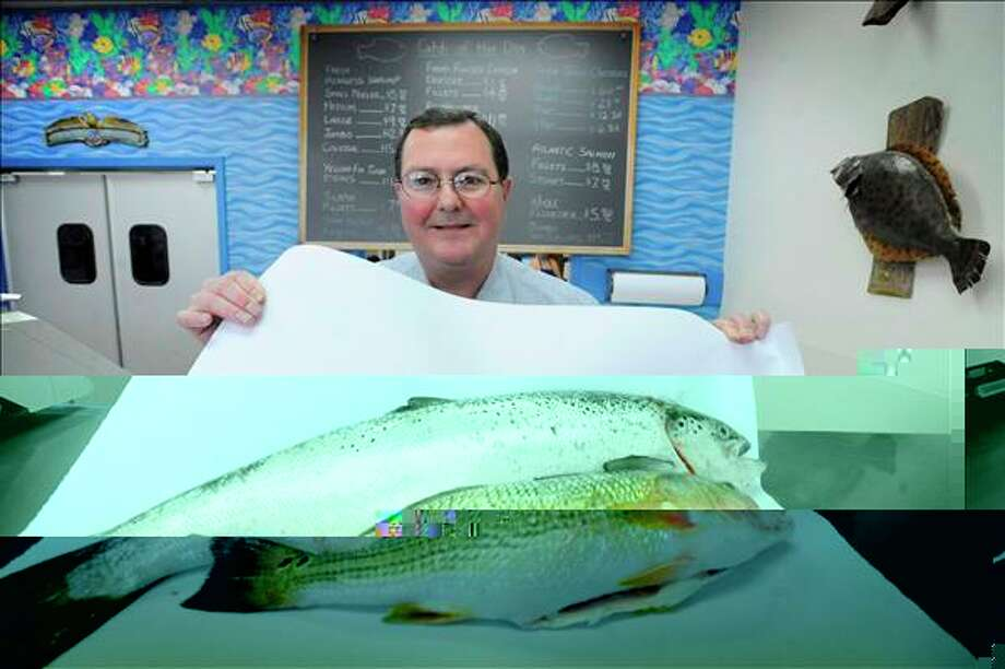 Steve Edwards, owner of Seafood Lover Inc. on Calder Ave. shows off two fish favorites for Lent, salmon, top, and redfish. Valentino Mauricio/The Enterprise