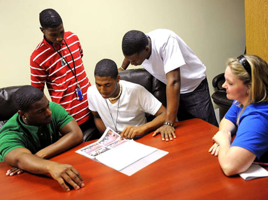 From left, Devin Williams, Leonard Thomas, Ben Johnson and Henry Mitchell look over photos from several trips to visit colleges this year. Ev'marie Peach, right, served as a mentor for the young men and several others in the Beaumont Housing Authority's Bound for Success program. Guiseppe Barranco/The Enterprise / Beaumont