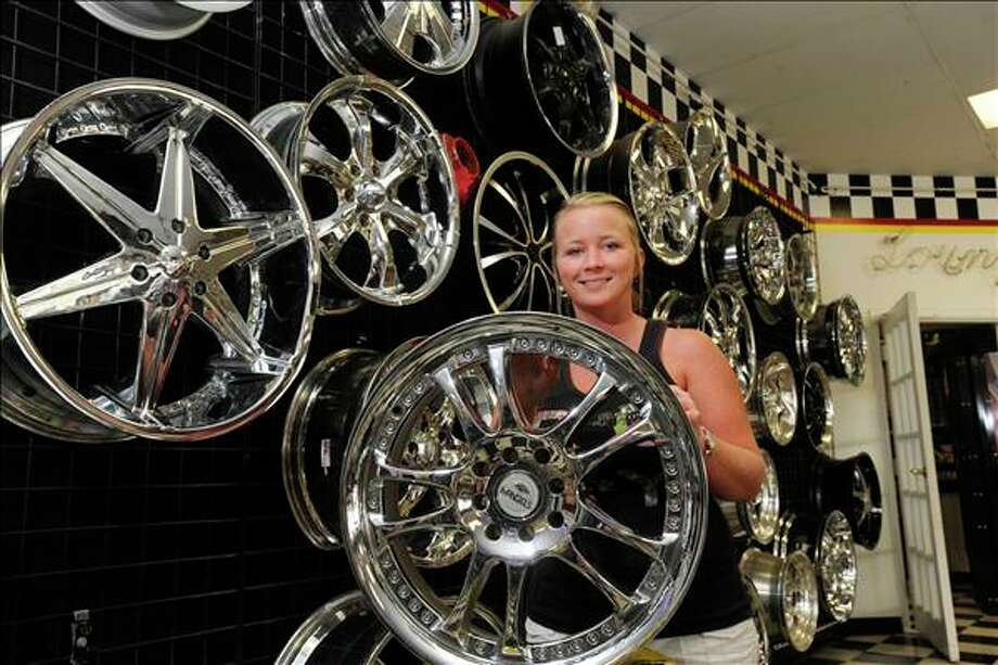 Robbin Dixon, a sales representative with Precision Automotive on College St., shows off a selection of the many rims in their showroom. Valentino Mauricio/The Enterprise