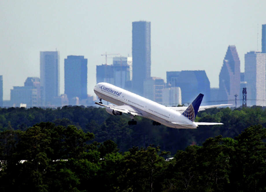 In this photo made Tuesday, April 27, 2010, a Continental Airlines plane takes off from George Bush Intercontinental Airport in Houston with city skyline in the background. Directors at Continental and United airlines have approved a deal that would combine them into the world's largest airline, a source with knowledge of the situation said on Sunday. (AP Photo/David J. Phillip) / AP2010