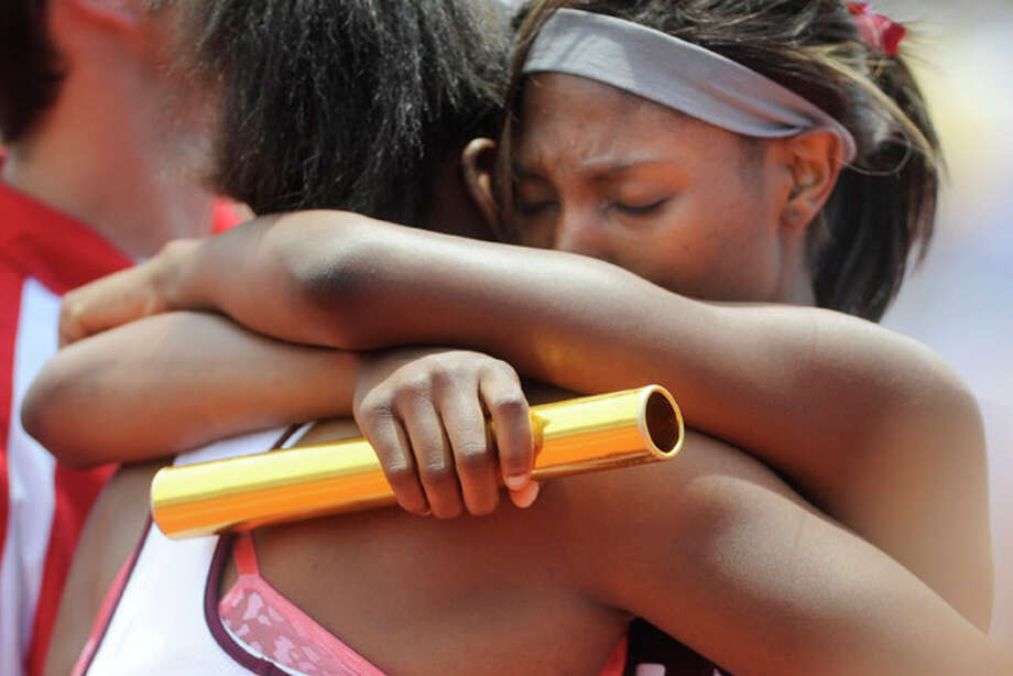 Silsbee's  Janeicia Myers, left,  and teammate Ashley Johnson share an emotional embrace, after Johnson sprinted to victory in the final 100 meters of the girls 3A 4x200 meter relay.  Along  with teammates, Beatrice Douglas and Cymone Toole, The Lady Tigers posted a winning time of 1:42.62 at the UIL State Track and Field Championships, Austin, Texas. Saturday, May 15, 2010. Valentino Mauricio/The Enterprise