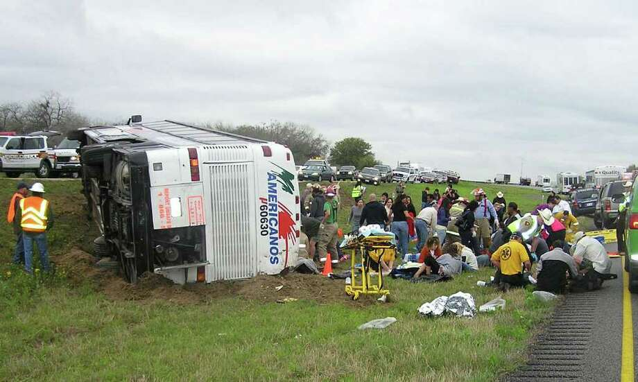 Officials and passersby tend to people injured after a tour bus headed for Mexico carrying 40 people overturned along a southern Texas highway on Tuesday, killing two people and injuring dozens more, officials said. Leon Zabava/The Associated Press / Pleasanton Express