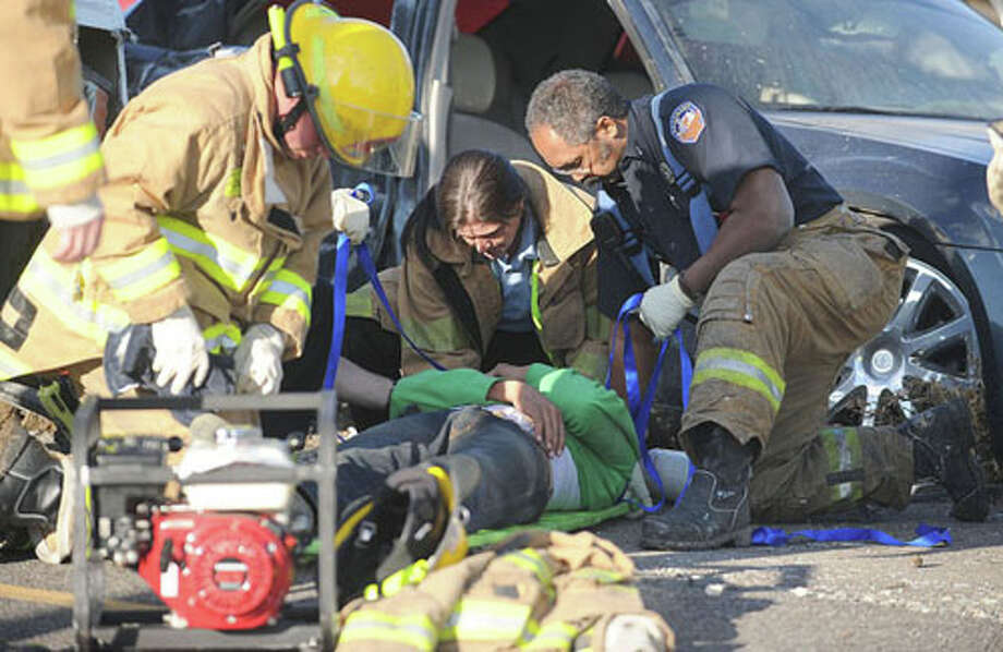 Emergency officials prepare a crash victim for an ambulance ride after a dump truck collided with two vehicles on U.S. 69 Freeway near Delaware Tuesday evening. Guiseppe Barranco/The Enterprise