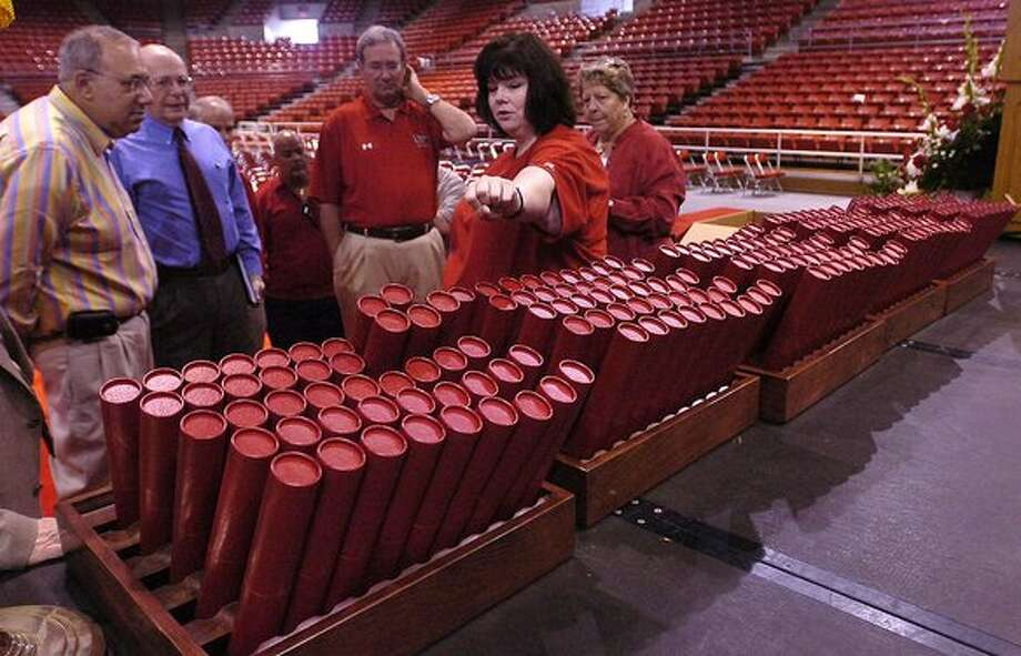 """Lamar University Registrar Sherry Wells, second from right, demonstrates to President James Simmons, and gathered Academic Deans and Administrators, how to handle the """"tubes"""" that will be handed to each student graduating Saturday.  The new """"tubes"""", which are made from the same material and have the school emblem on it, replace the binders given to students in the past that held their diplomas.    Dave Ryan/The Enterprise / Beaumont"""