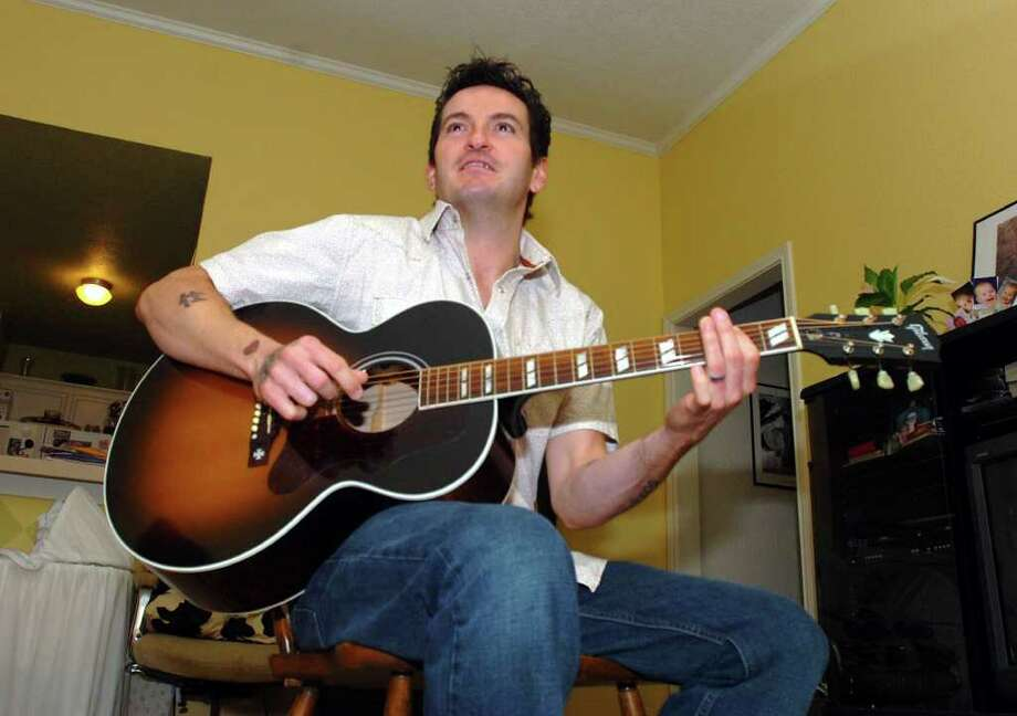 Mike Zito plays his acoustic guitar in the living room of his Nederland home. Pete Churton/The Enterprise / Beaumont