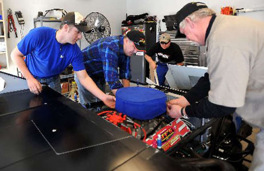 Johhny Brown, Pat Brown, Grant Brown, and David Brown work on one of their Dust Devil team race cars at their garage in Lumberton.  Tammy McKinley/ The Enterprise
