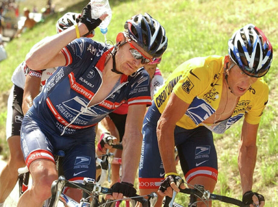 This July 22, 2004, photo shows Lance Armstrong, right, straining in the ascent of the La Croix Fry pass as teammate Floyd Landis pours water over his neck during the 17th stage of the Tour de France cycling race between Bourg-d'Oisans and Le Grand Bornand, French Alps. Disgraced American cyclist Floyd Landis has admitted to systematic use of performance-enhancing drugs and accused seven-time Tour de France champion Lance Armstrong of involvement in doping, the Wall Street Journal reported Thursday. AP Photo/Bernard Papon