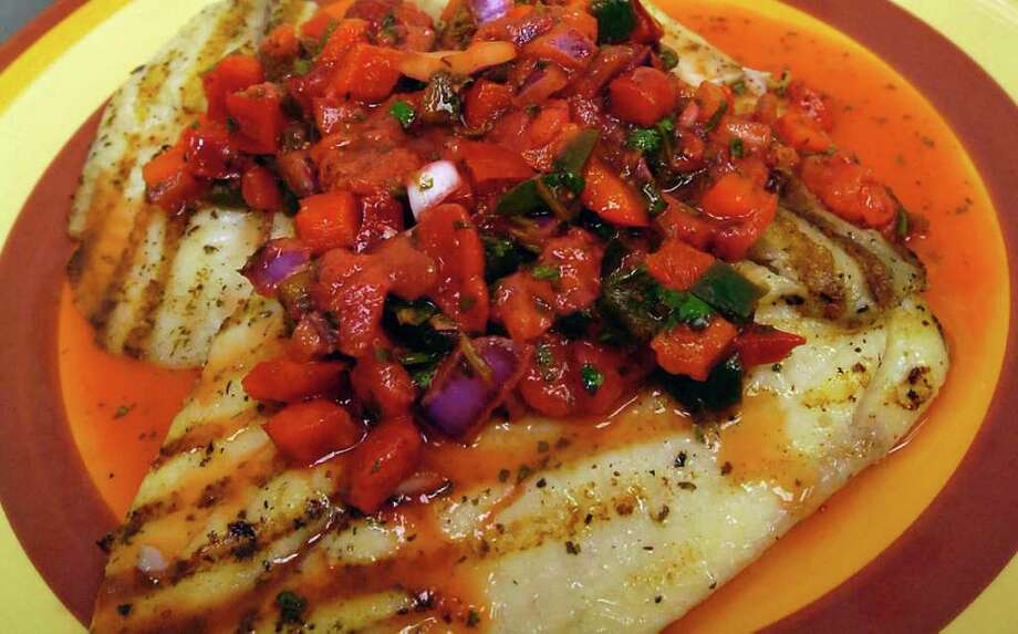 Tabetha Franklin, owner of the Main Dish Studio Kitchen, has an idea for those looking for another way to cook fish during the Lenten season.   Grilled Tilapia covered with a Strawberry Salsa.   Dave Ryan/The Enterprise / Beaumont