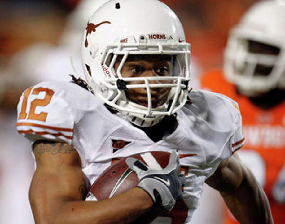 Texas safety Earl Thomas, left, takes his third-quarter interception back 31 yards for a touchdown as Oklahoma State's Hubert Anyiam, right, trails, in an NCAA college football game in Stillwater, Okla., Saturday, Oct. 31, 2009. Texas won 41-14. (AP Photo/Sue Ogrocki) / AP