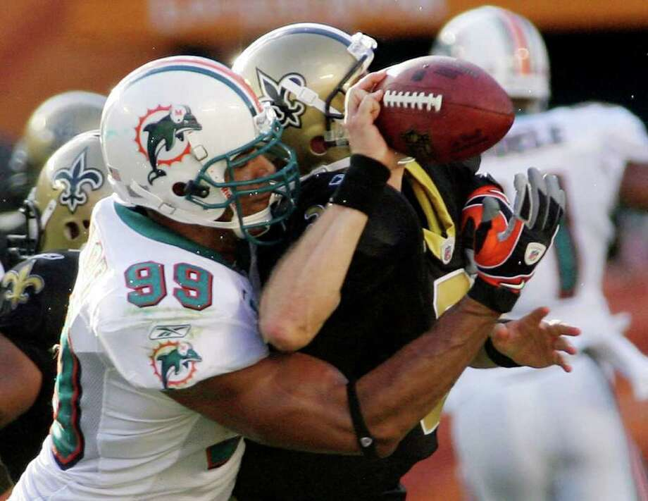 FILE - In this Oct. 25, 2009, file phot,o New Orleans Saints quarterback Drew Brees is sacked by Miami Dolphins linebacker Jason Taylor (99) during the second quarter of an NFL football game in Miami. Taylor realizes he has a lot of work to do to endear himself to New York Jets fans. It could all start with a few early season sacks as he tries to take advantage of what might have been his last shot at continuing his NFL career. (AP Photo/Jeffrey M. Boan, File)