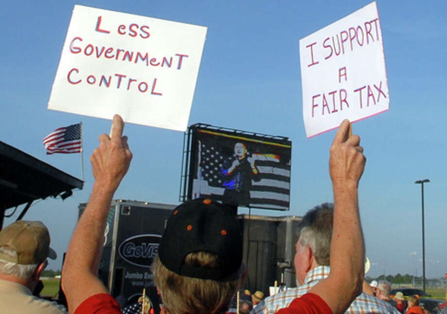 Curtis Walters of Kountze holds signs up at the tax day Tea Party at Ford Park Thursday night. Beth Rankin/The Enterprise / Beaumont