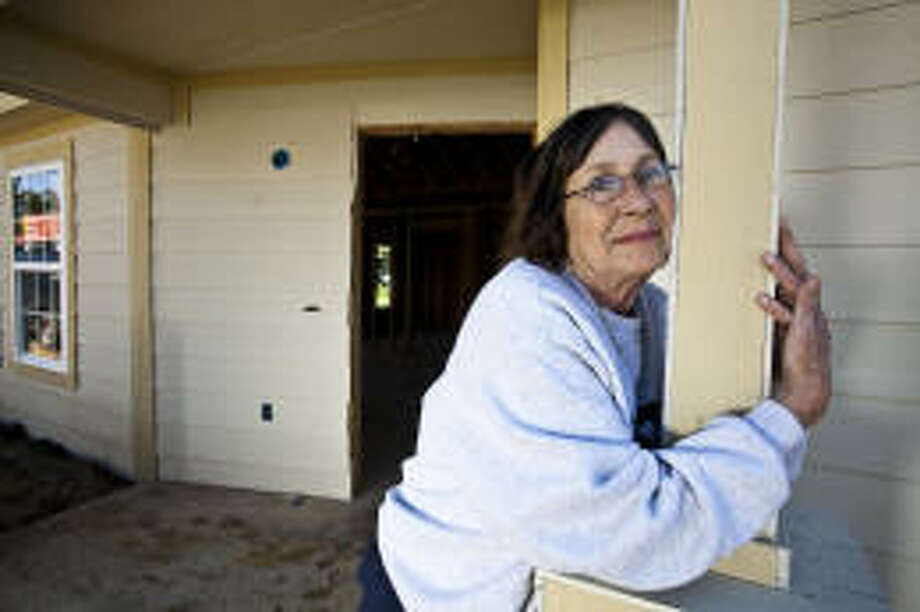 Janelle McDonough stands next to her new home, which she loves, last week in Port Arthur. McDonough currently lives in a FEMA trailer but will move into the experimental house soon. Eric Kayne/Houston Chronicle