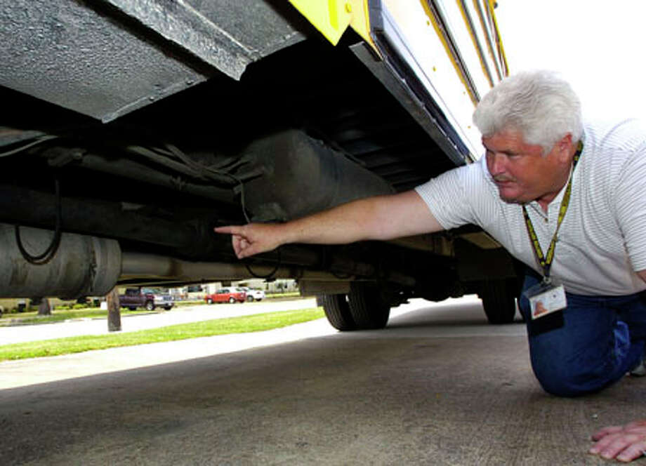 Charles Polk, transportation supervisor for Nederland ISD, describes the function of a retrofitted muffler-looking device underneath a 2004 school bus.   The cleanable device is designed to remove soot and harmful fumes from the air. The district bought it through a grant program through TCEQ. Dave Ryan/The Enterprise / Beaumont