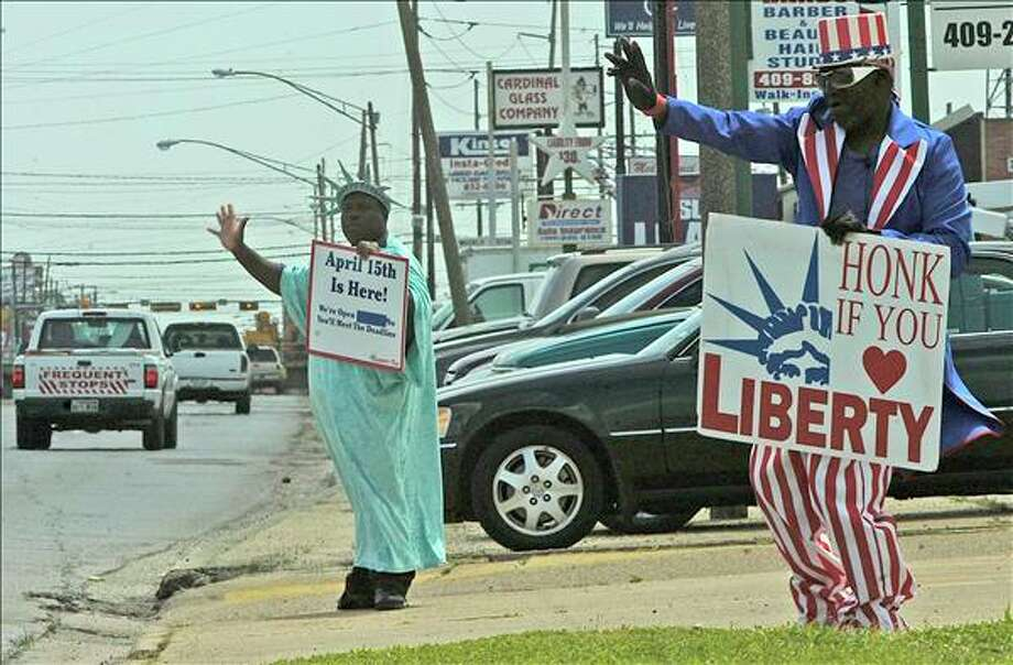 Uncle Sam and Lady Liberty remind the public to get their income taxes done by Thursday?s annual deadline for returns. Dave Ryan/The Enterprise