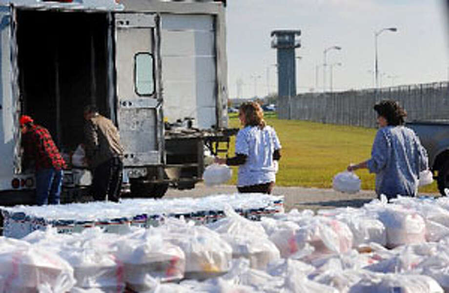 Volunteers transport plate lunches for prison guards at the Stiles Unit on Thursday as a thank you and precursor to Friday's inmate revival conducted by the Bill Glass Crusade. Guiseppe Barranco/The Enterprise