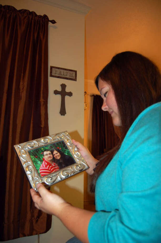Hope Adkins looks at a photo of her and her husband, Brandon Adkins. Newsboy photo/Heather Cooper