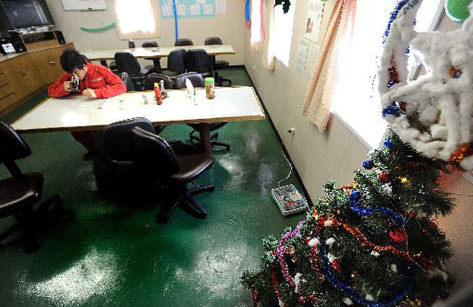 Christmas tree and other decoctions line the cafeteria of the Maren Bulker where its Filipino sailors will celebrate the holiday somewhere in the Gulf of Mexico. Aristeo Jocson sips a cup of tea while the ship was docked at the Port of Beaumont on Tuesday. Guiseppe Barranco/The Enterprise