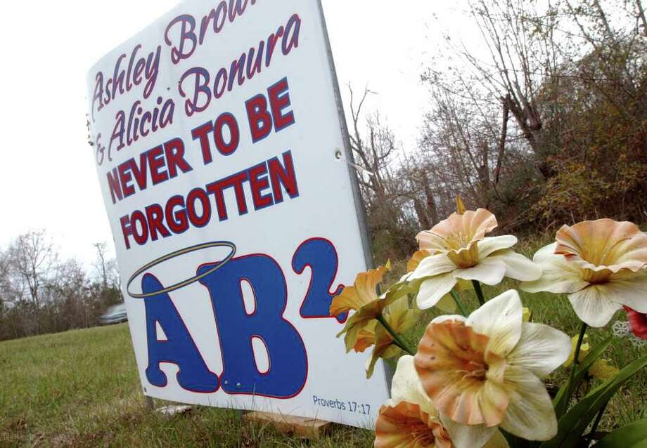 A sign and flowers remembering Ashley Brown and Alicia Bonura is seen off US 90.