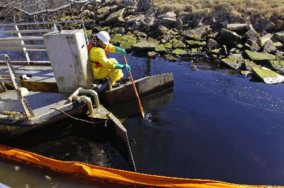 More than 11 miles of oil booms have been deployed in the 9 mile stretch of the Sabine-Neches Waterway to clean up the 460,000 gallons of spilled oil from the Eagle Otome. In this boomed-off cove of oil, an employee of Oil Mop Inc. uses a paddle to direct the oil/water mixture into the mouth of one of the 27 oil skimmer boats.  Dave Ryan/The Enterprise