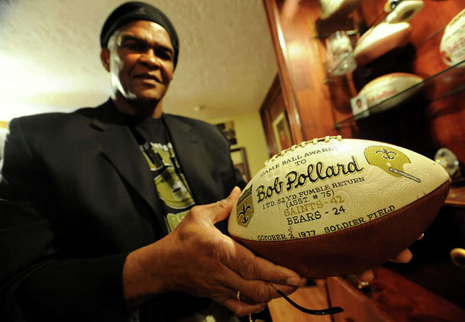 Bob Pollard shows off one of his game balls from when he played with the New Orleans Saints at his home, Friday. Tammy McKinley/ The Enterprise