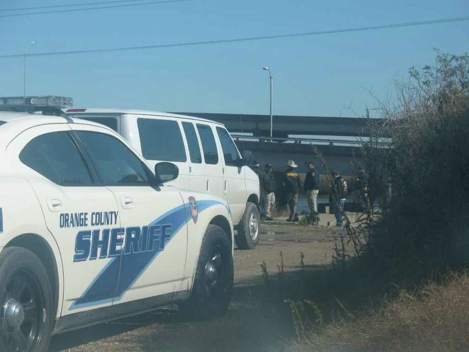 Deputies with the Orange County Sheriff's Office and Texas Parks and Wildlife await news of the search and rescue mission of a man who jumped off the Veteran's Memorial Bridge this morning. Amy Moore/The Enterprise