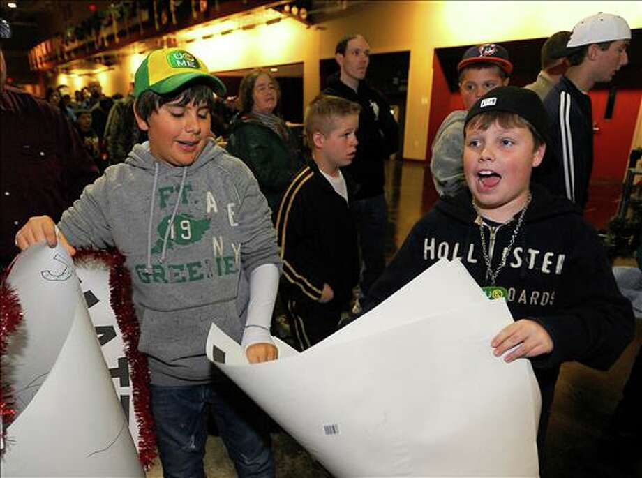 Matthew Taylor, 11, and Baylor Blackburn, 11, carry signs into the WWE Wrestling event Monday night. Guiseppe Barranco/The Enterprise