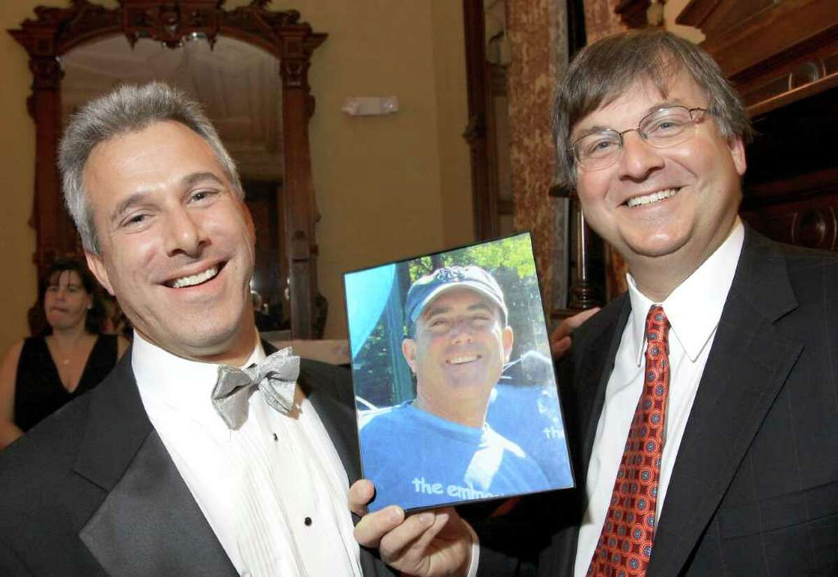 Jerry Goldstein, shown in photograph, was so disappointed he couldn't attend the Down Syndrome Aim High Resource Center Inaugural Gala and Casino Night that friends brought a picture of him to the gala and photographed it with partygoers, including Scott Burack, left, and Bill Golderman. The event was held at Canfield Casino in Saratoga Springs. (Joe Putrock / Special to the Times Union)