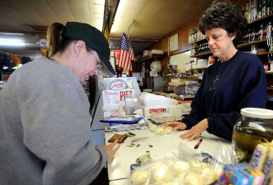 DeDe Duran purchases a couple of packages of hard boiled eggs on Friday from Katheryne Knox at Veteran's Grocery store in Orange. Knox boils, peels, and adds salt and pepper to the eggs before packaging them for sale. Tammy McKinley/ The Enterprise