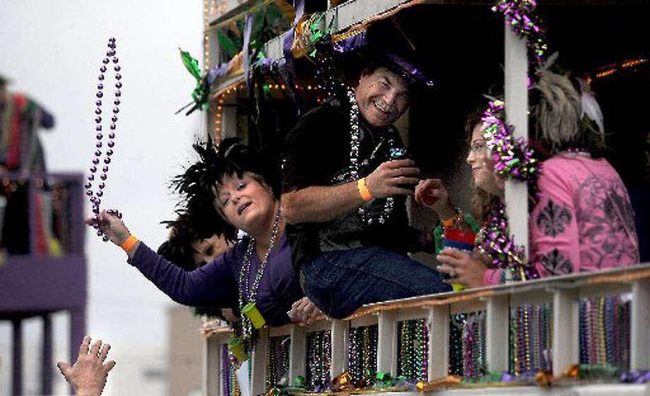 Revelers throw beads during the 2009 Mardi Gras parade in Orange.  Tammy McKinley/The Enterprise