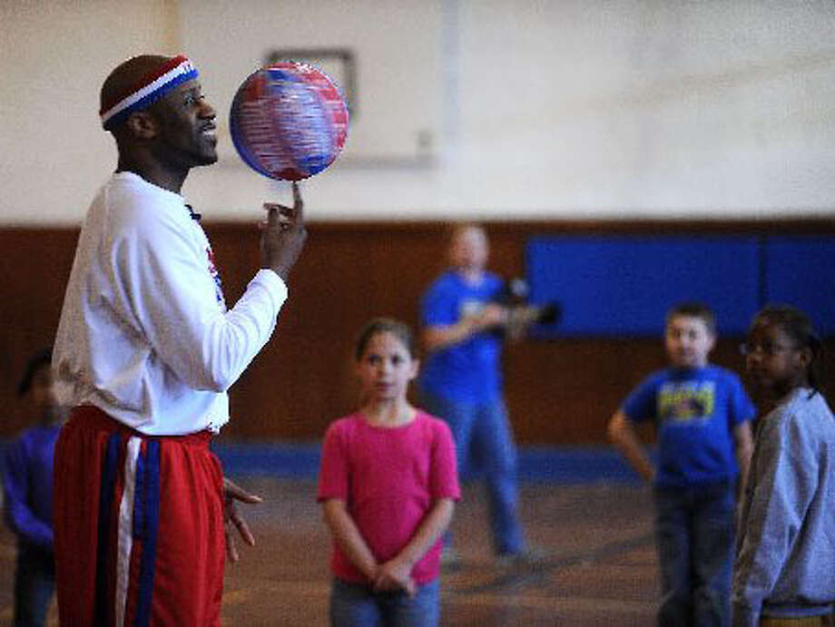 """The Harlem Globetrotter's Andre """"Hot Shot"""" Branch spins a ball for Hamshire Fannett Elementary students last week. The famous basketball team will exhibit their skills at Ford Park tonight. Guiseppe Barranco/The Enterprise"""