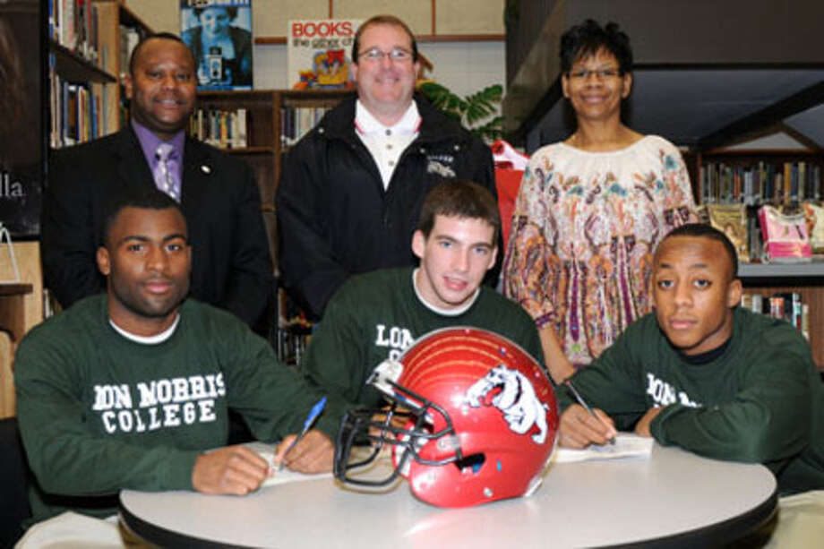 Kadarroe Rawls, Shane Savant,  Cedric McGill sign letters of intent to play at Lon Morris next year. Pictured back row, are  JHS principal Victor Williams, Coach Bickham, Cedric   McGill's mother Beverly Bean.