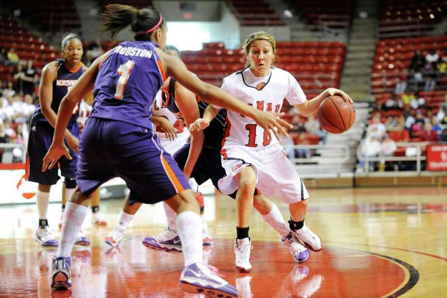 Lamar guard Jenna Plumley, center, tries to drive around Northwestern State defender Brittiany Houston during the first half of their game at the Montagne Center on Saturday. Valentino Mauricio/The Enterprise / Beaumont