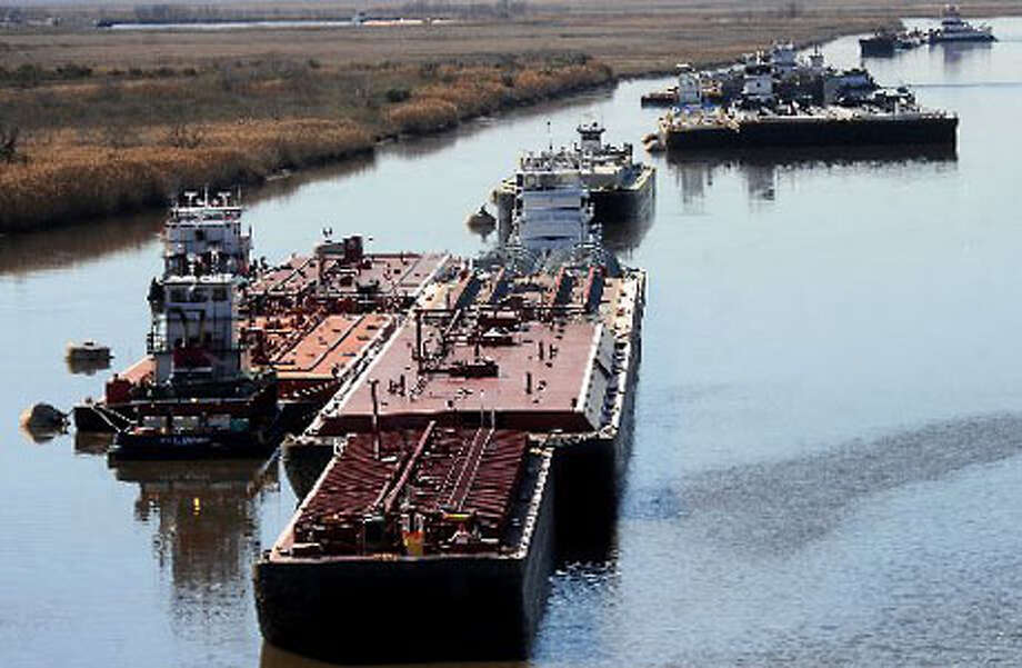 Tugs and barges wait to pass through the shipping channel as an oil spill from Saturday's collision is cleaned up on the Intracoastal Canal near Port Arthur. Tammy McKinley/The Enterprise