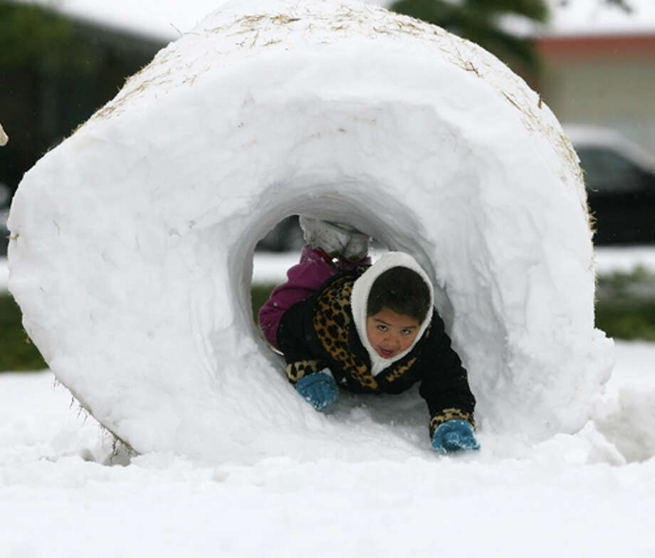 Jocelyn Vargas crawls through a snow donut made by family members during an outing to Album Par in El Paso. Victor Calzada/The Associated Press / El Paso Times