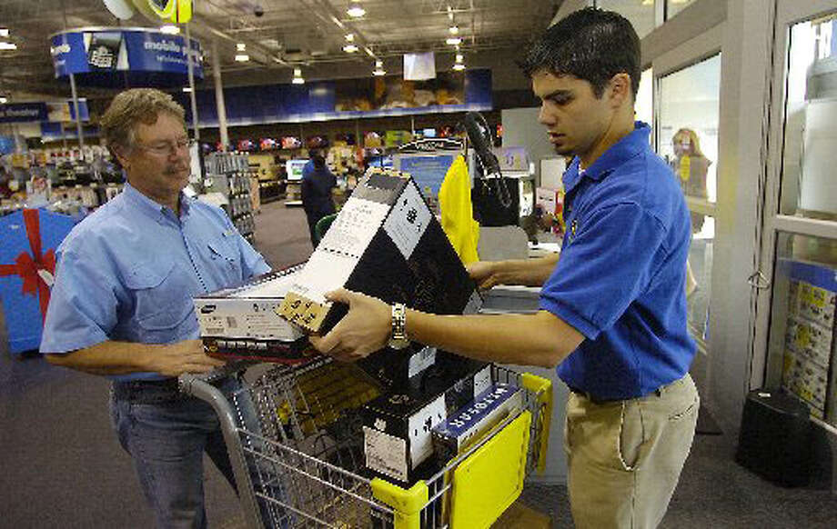 Jamie Hoskinson, left, a Beaumont resident, waits for Best Buy employee Adam Lovett, right, to check his Christmas purchases, before leaving the store. Cardboard boxes, from purchases such as this, if reused somewhere else around the house, will help reduce the household carbon footprint. Dave Ryan/The Enterprise