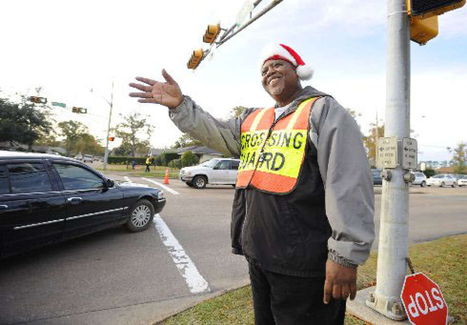 "Crossing guard Larry Payne, ""The Waver,"" works his corner at Dowlen Road and Westgate Drive near Marshall Middle School. Payne earned his name from his habit of waving at every passing driver. He's acquired a large and devoted following. A Facebook page created in his honor already has more than 1,200 fans.  Valentino Mauricio/The Enterprise"