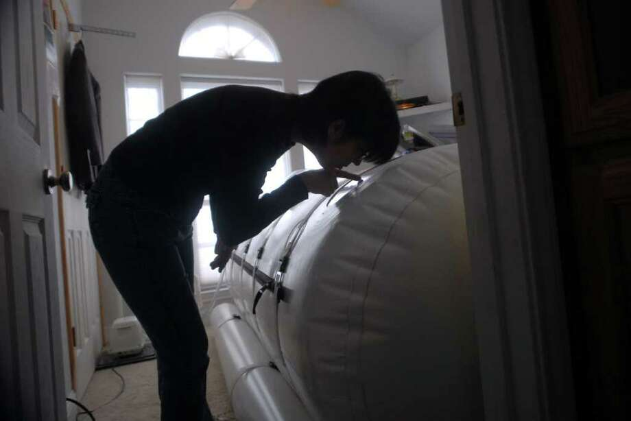 Melinda Handley, Richard's mother, checks on him once the hyperbaric chamber has inflated and pressurized. Beth Rankin/The Enterprise