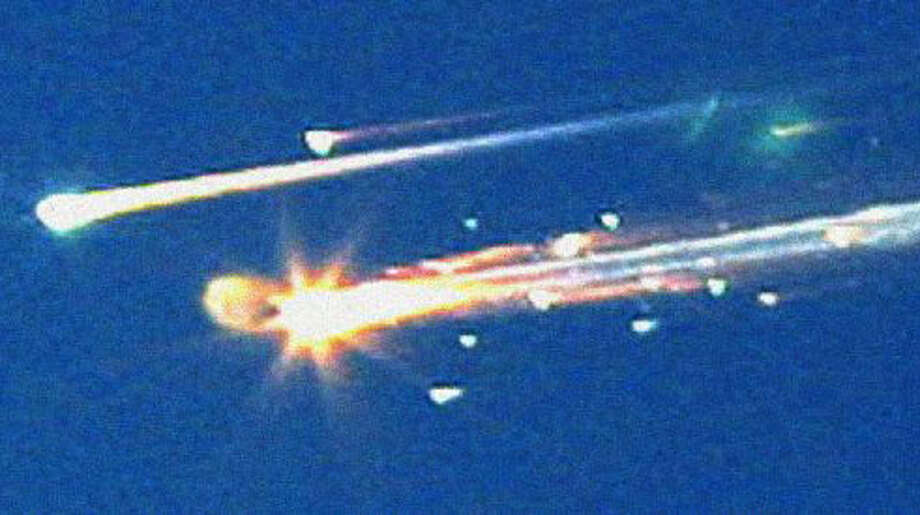 In this Feb. 1, 2003, file photo, debris from the space shuttle Columbia streaks across the sky over Tyler.  The Associated Press
