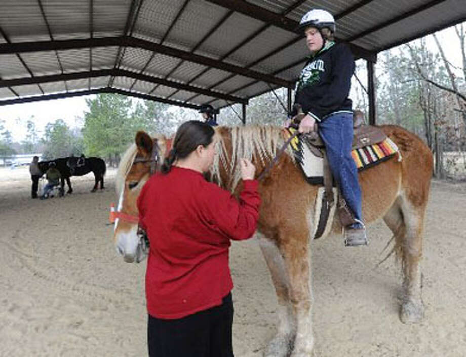 Kim Gauthier, left, owner of The Healing Hoof, a horse-riding therapy program in Evadale, works Thursday with student Reed Rankin, 14, of Kountze during a riding session.  Valentino Mauricio/The Enterprise