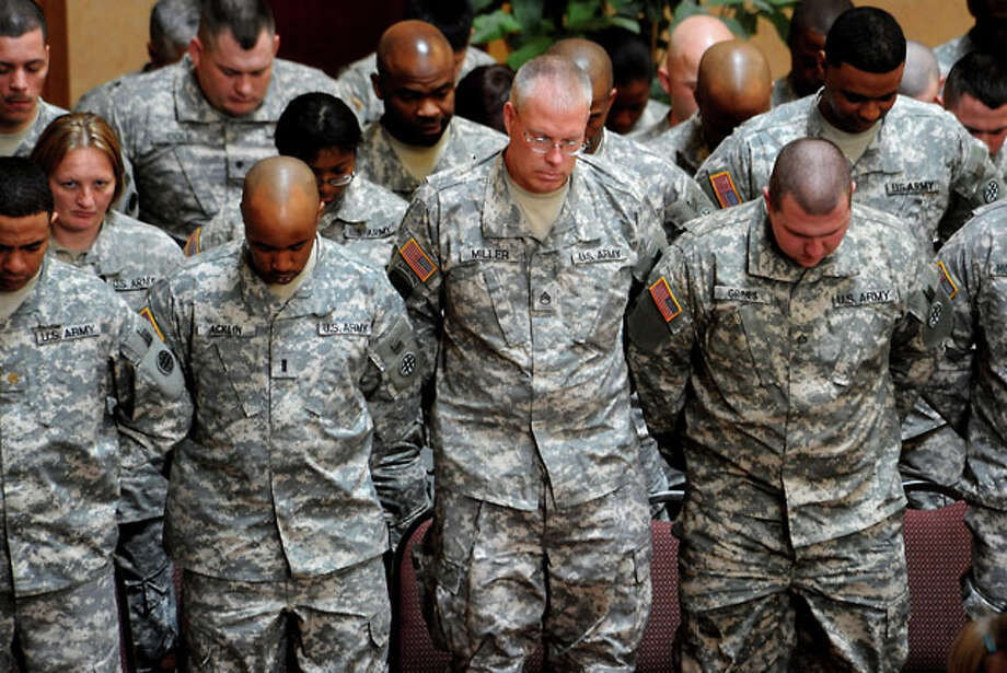 Soldiers pray during the mobilization ceremony for the 373rd Combat Sustainment Support Battalion at the Holiday Inn in Beaumont,  Saturday. The unit will be deploying to Iraq after training at Fort Lewis, WA.  Tammy McKinley/ The Enterprise
