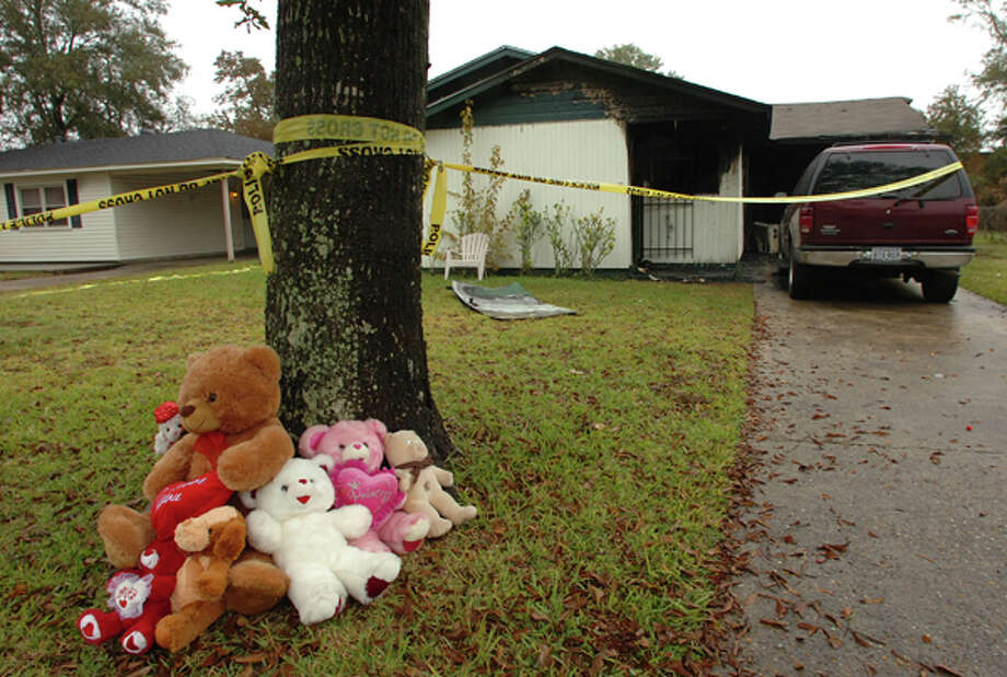 Neighbors placed stuffed animals in the yard of 1241 Palm Drive in Orange where a house fire claimed the lives of 3 and 4-year-old sisters early Monday. One firefighter was injured in the rescue effort. Pete Churton/The Enterprise / Beaumont