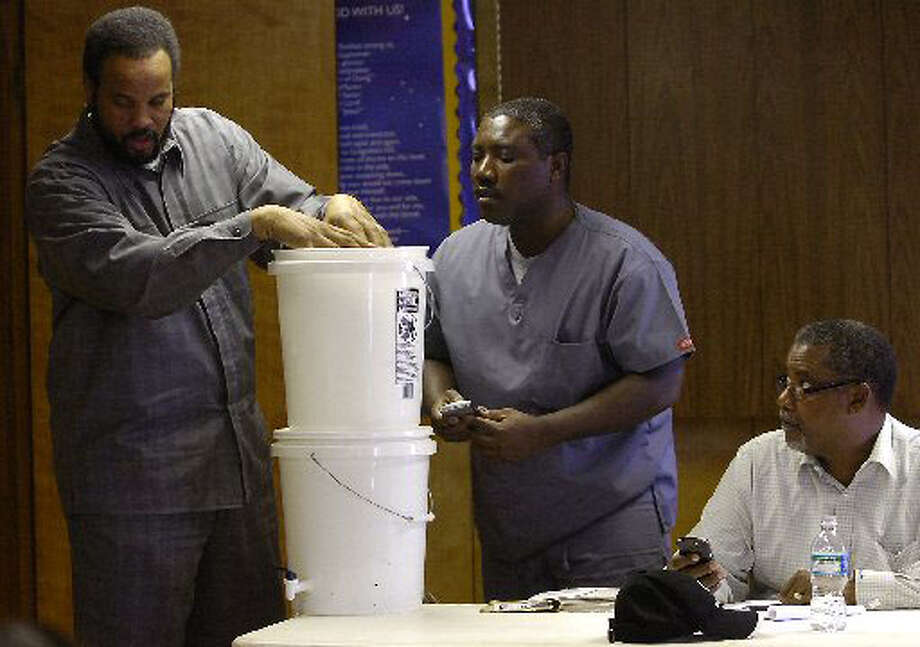 Pastor Randy Vaughn, right, of Mt. Sinai Missionary Baptist Church, listens as his Administrative Assistant explains how the water filters work. Dave Ryan/The Enterprise