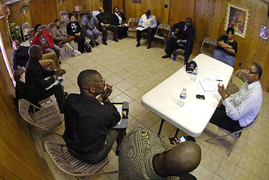 Pastor Randy Vaughn, right, of Mt. Sinai Missionary Baptist Church in Port Arthur, leads a discussion of the Haiti Christian Missionary Support Group as they work on a response plan to help quake victims.  Dave Ryan/The Enterprise