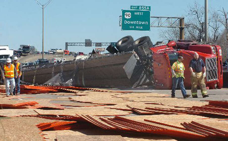 Interstate 10 westbound traffic will be tied up for awhile Tuesday to allow for the clean up of a load of particle board that spilled onto the road when a westbound truck flipped onto its side about 2 p.m. Officials were investigating the cause of the mishap.  Pete Churton/The Enterprise