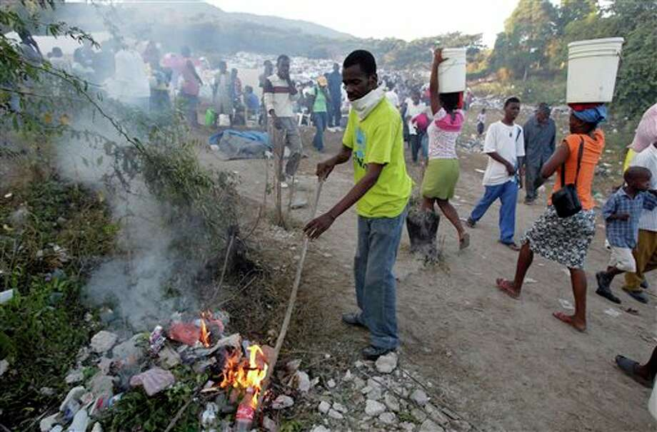 Yonel Regis, a pastor from a local church, burns trash at a refugee camp set up on a golf course in Port-au-Prince, Tuesday, Jan. 19, 2010. A powerful earthquake hit Haiti last week.  (AP Photo/Jae C. Hong)
