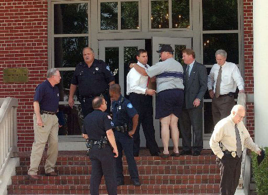 Beaumont police officers and others, including attorney Trent Bond who restrained suspect Richard Joseph, gather at the scene of the murder of Beaumont attorney Cris Quinn in June 2002. Dave Ryan/The Enterprise