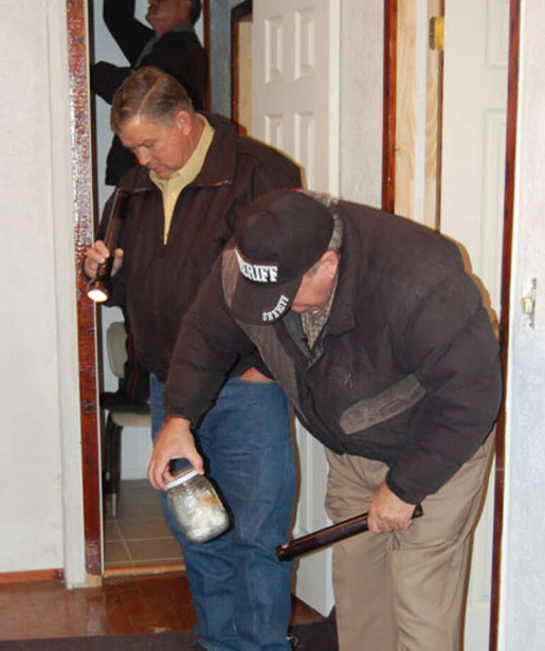Jasper County Sheriff Mitchel Newman inspects a bottle during a drug raid in Mount Union.