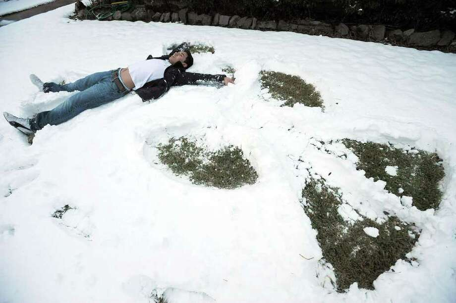 Ricky Jimenez builds a snow angel in Beaumont when Southeast Texas was blanketed with snow in Dec. 2008. Could SETX see flutters of flurries as the temperatures approach freezing this week? Enterprise file photo / Beaumont
