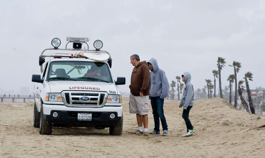 A Seal Beach lifeguard stops to tell a group of people that Seal Beach is closed for safety reasons after the earthquake in Chile and the possible tsunami surge along the West Coast. AP Photo/Sam Gangwer / The Orange County Register