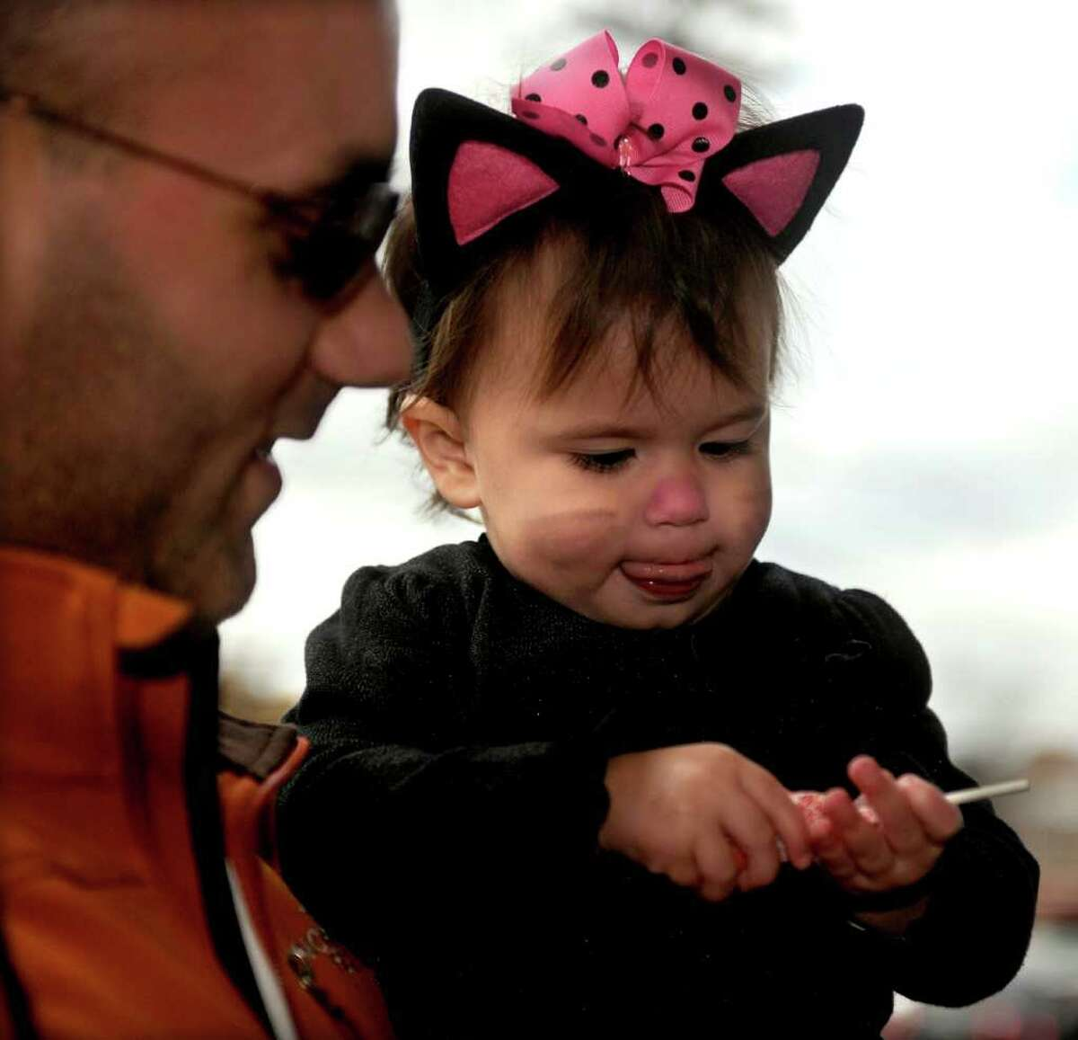 Lily Cina, 1, takes a look at her lollipop during the Trick or Treat on Safety Street event in Fairfield on Friday, October 29, 2010.